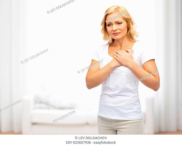 people, healthcare, heart disease and problem concept - unhappy woman suffering from heartache over living room background