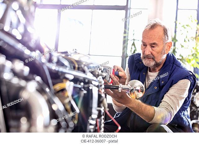 Senior male motorcycle mechanic fixing motorcycle in workshop