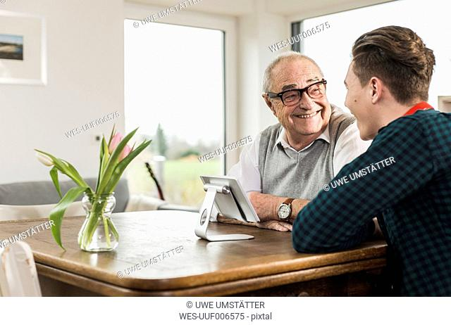 Happy senior man and his grandson sitting at table in the living room