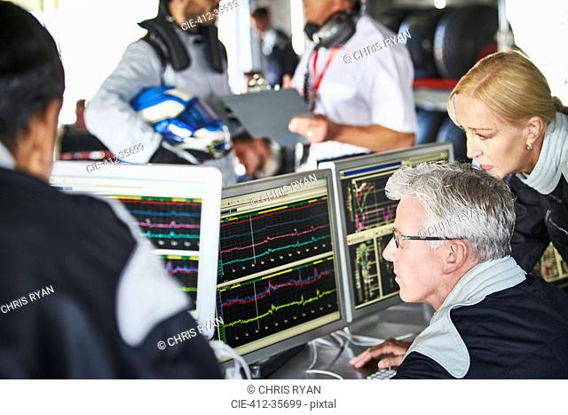 Formula one team reviewing diagnostics telemetry data on computers