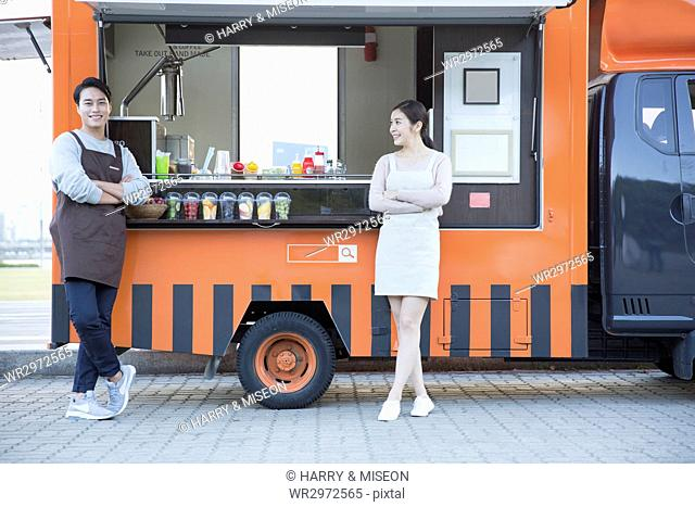 Young smiling vendors posing in front of food truck