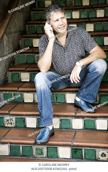 Senior man sitting on a staircase and talking on a mobile phone