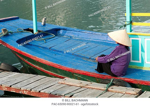 South East Asia, Vietnam, Ha Long Bay, Portrait of a Vietnamese woman sitting on docked fishing boat, side view