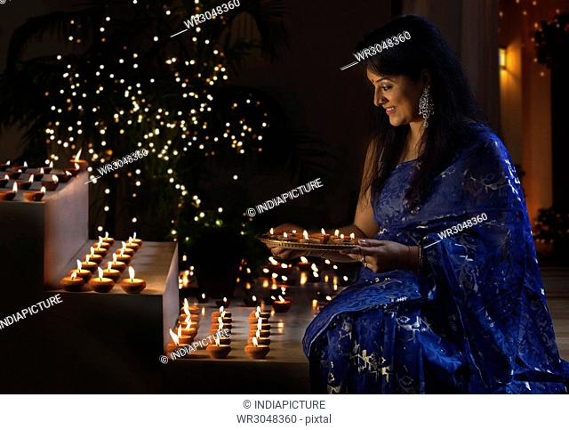 Woman arranging oil lamps on steps at a diwali festival