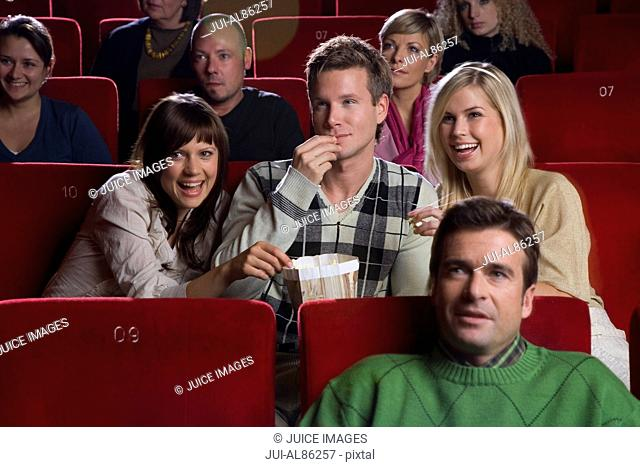 Man with two women in movie theater