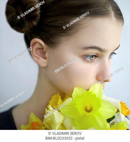 Pensive Caucasian girl holding yellow flowers