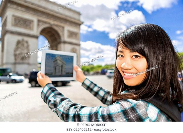 View of a Young attractive asian tourist taking pictures in Paris