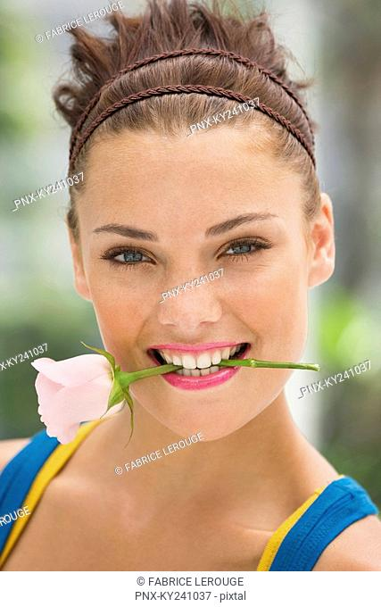 Fashion model holding rose between her teeth