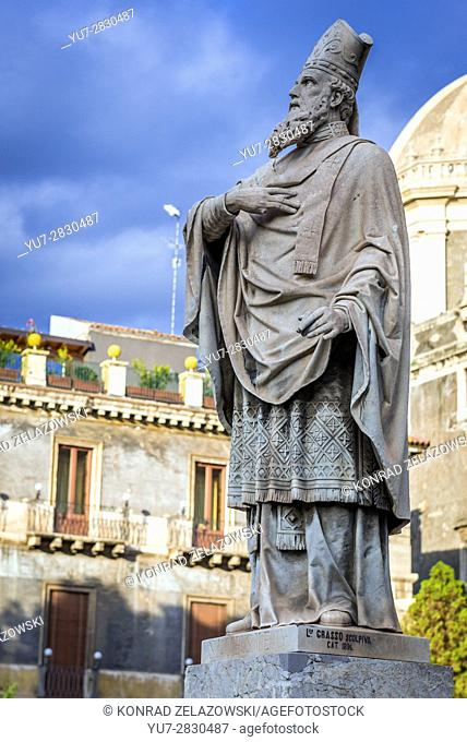 Statue of a saint in front of Roman Catholic Metropolitan Cathedral of Saint Agatha on Cathedral Square in Catania city, Sicily Island, Italy