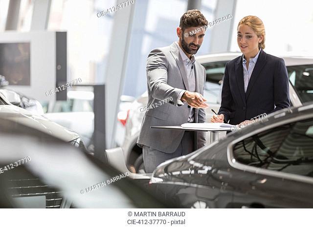 Car sales people meeting, examining new car in car dealership showroom