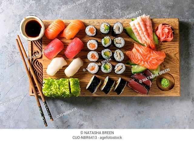 Sushi Set nigiri sashimi and sushi rolls on wooden serving board with soy sauce and chopsticks over grey concrete background. Flat lay, space