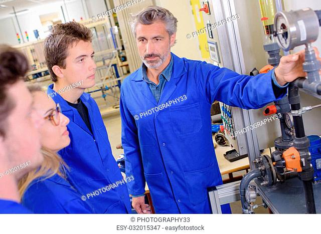 Teacher showing machinery to apprentices