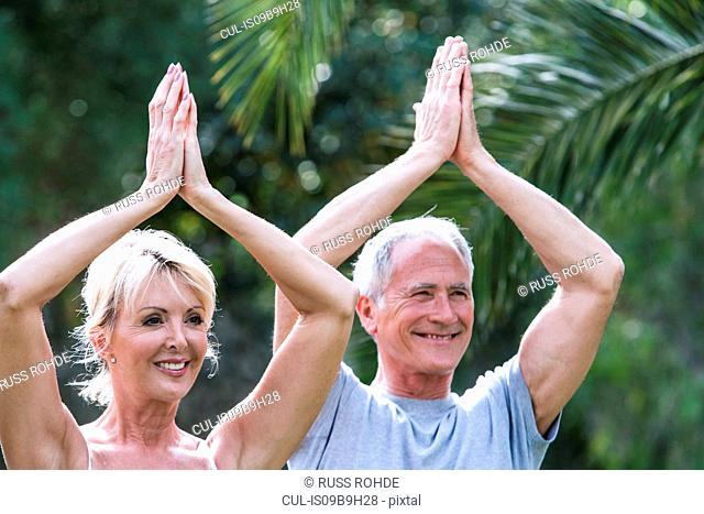 Couple, hands together, arms raised in yoga position