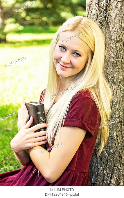 A young woman with long blond hair holding her Bible close to her chest while spending personal devotional time outdoors in a park in autumn; Edmonton, Alberta