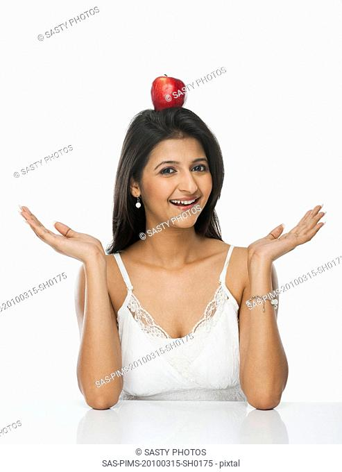 Woman balancing an apple on her head and smiling