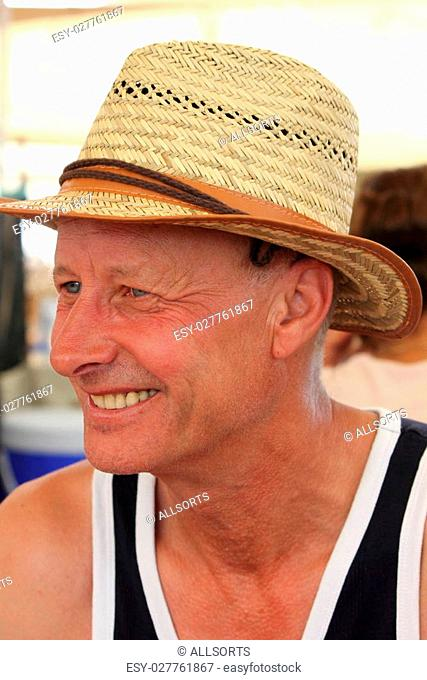 A mature white male smiling and wearing a straw hat