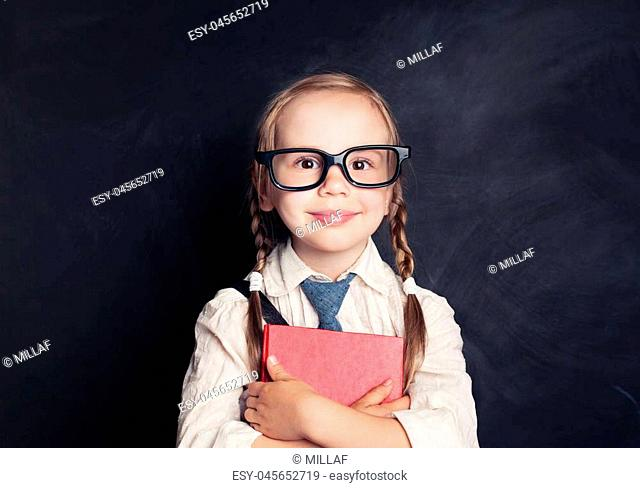 Smiling Child Girl with Book on Blackboard Background with Copy space. Small Girl in Glasses. Back to School Concept