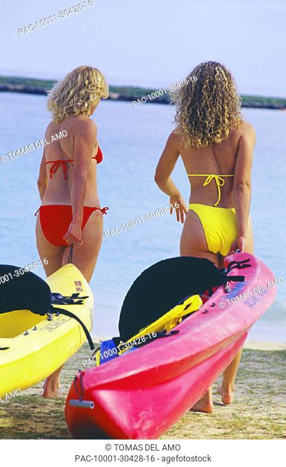 Two blonde women pulling kayaks into ocean, walking on sand