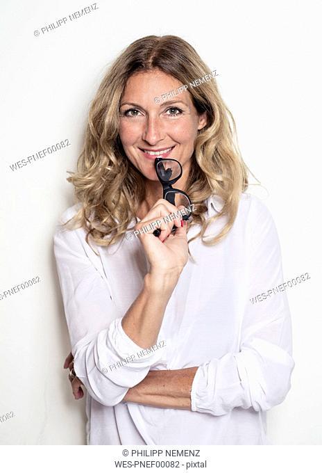 Portrait of smiling businesswoman holding glasses