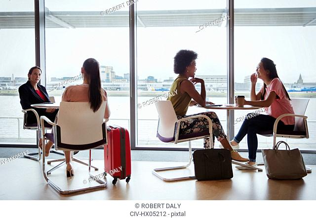 Businesswomen talking in airport business lounge
