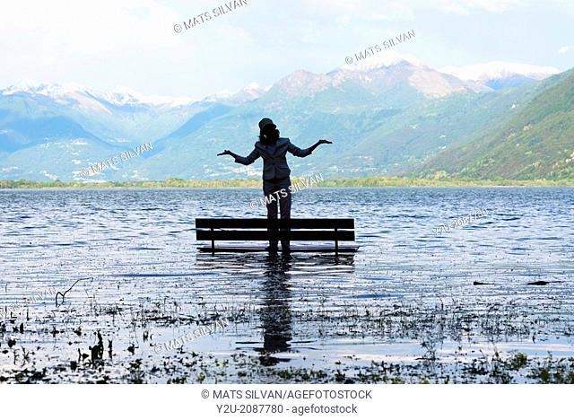 Woman standing on a bench in a flooding alpine lake maggiore, with snow-capped mountain in background in ticino switzerland