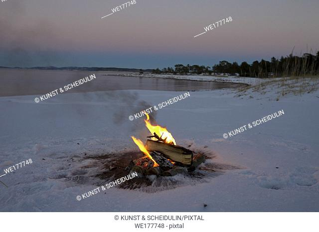 Camp fire in the snow on a beach
