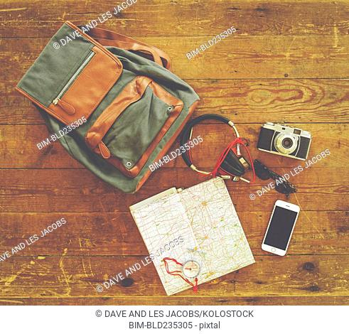 Backpack with map and travel accessories on wooden table