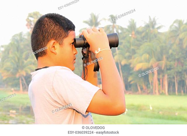 Thai boy looking the nature through binoculars