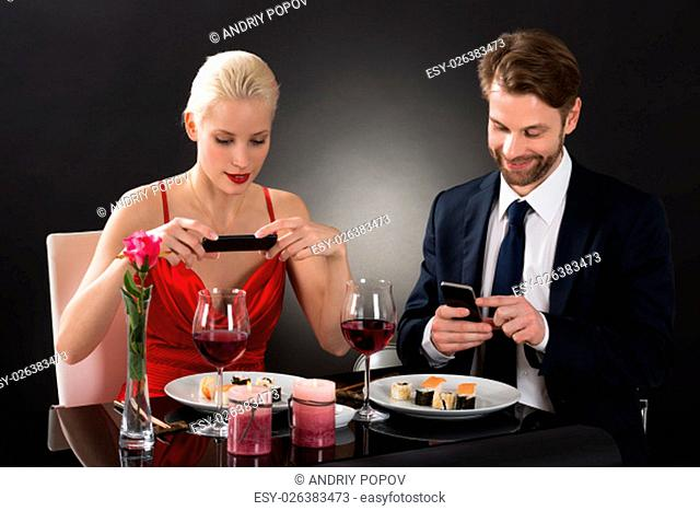 Young Couple Taking Picture Of Food With Their Smartphone In A Restaurant