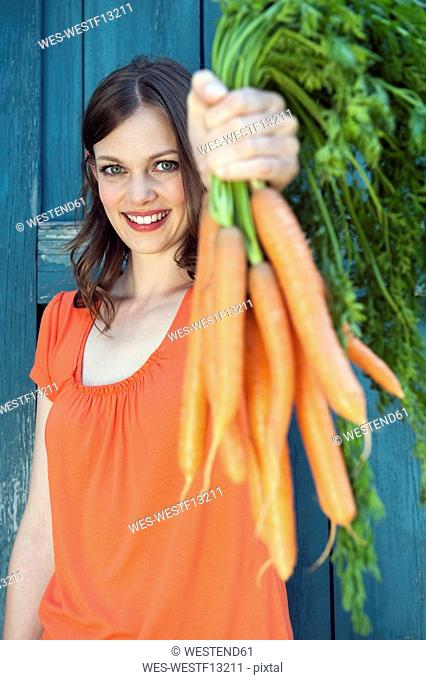 Germany, Bavaria, Woman holding bunch of carrots