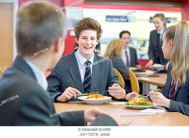 Smiling high school students eating lunch in cafeteria