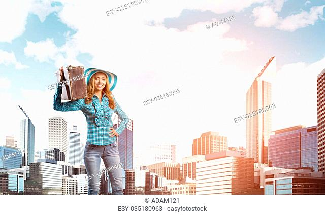 Beautiful woman traveler in hat with suitcase on modern city background