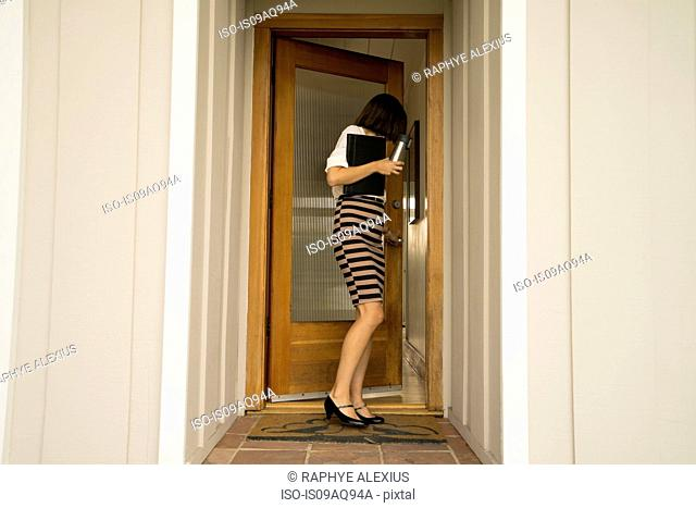 Businesswoman closing house front door