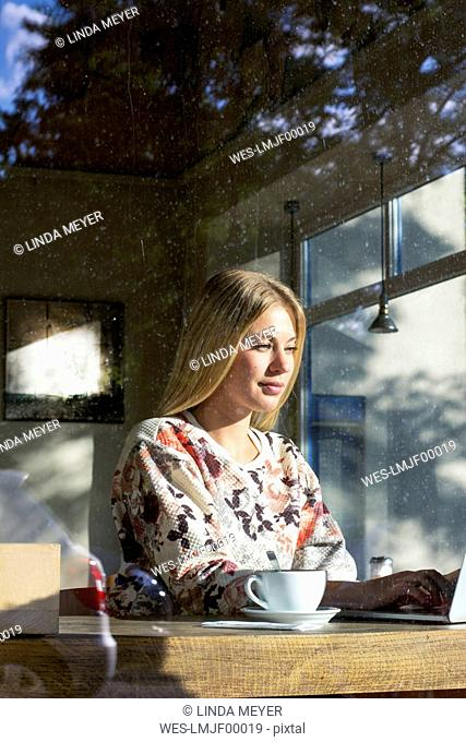 Portrait of blond woman working on laptop in a cafe