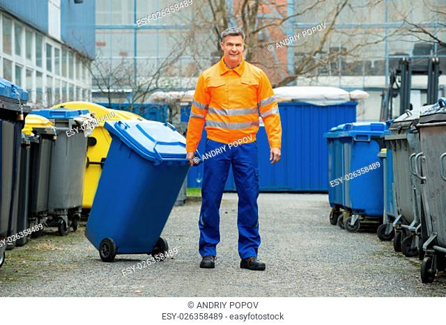 Happy Male Worker Walking With Dustbin On Street During Day