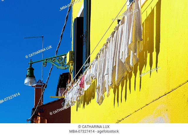 Venetian lagoon, island of Burano, yellow house with laundry
