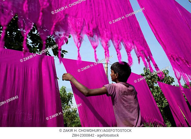 A boy drying dyed cloths under sun,he is helping family business