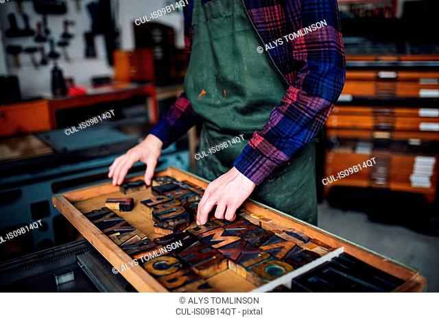 Crop of young craftsman looking through tray of wooden letterpress letters in print workshop