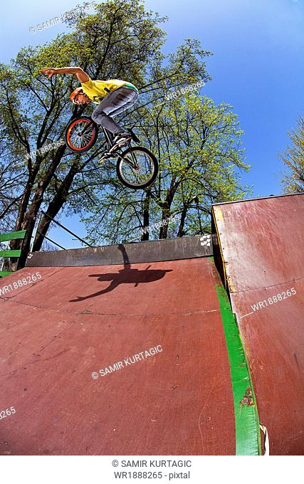 Teenager doing BMX bike stunt in skateboard park, Osijek, Croatia, Europe