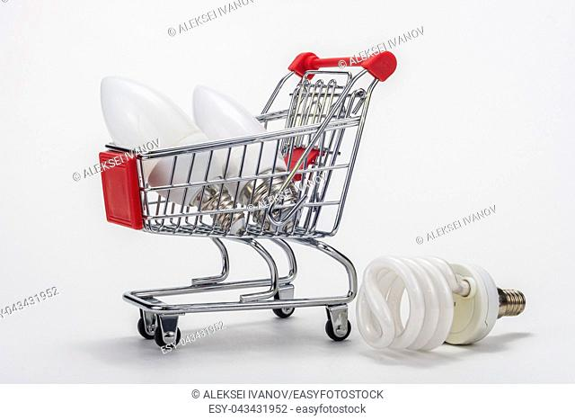 In the grocery cart are LED bulbs, next is an energy-saving light bulb