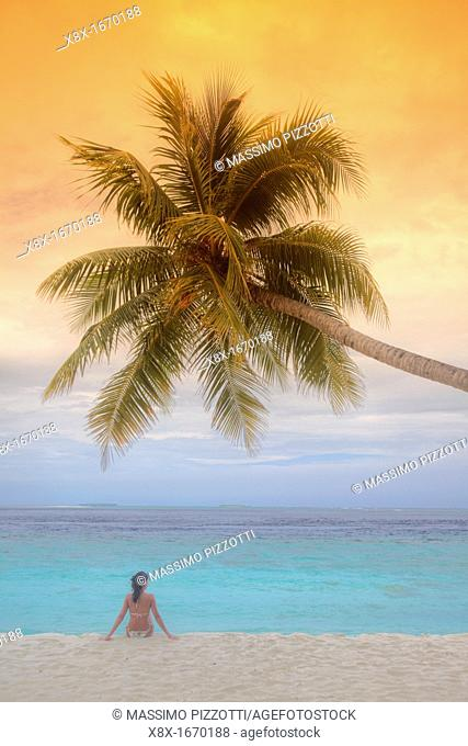 Girl seated under a palm on seashore, Biyadhoo island, Maldives