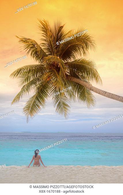 Girl seated under a palm on seashore, Biyadhoo island, Maldives