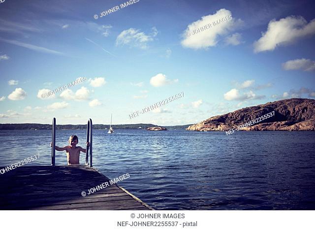 Boy on ladder at jetty