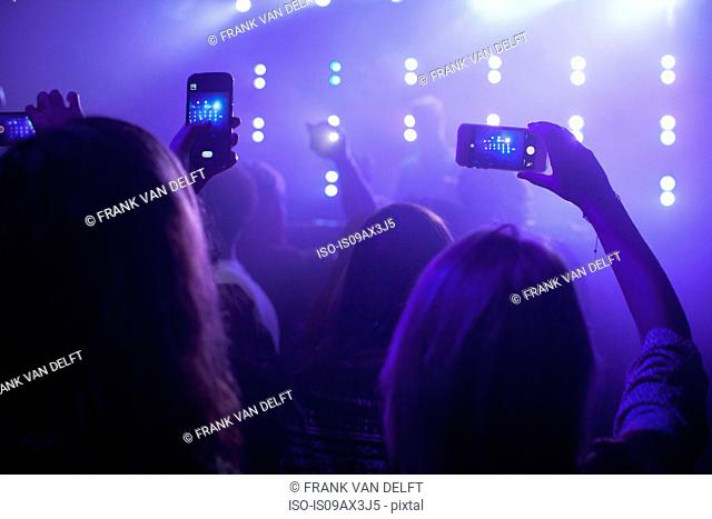 group of people at concert, taking photographs of stage, using smartphones, rear view
