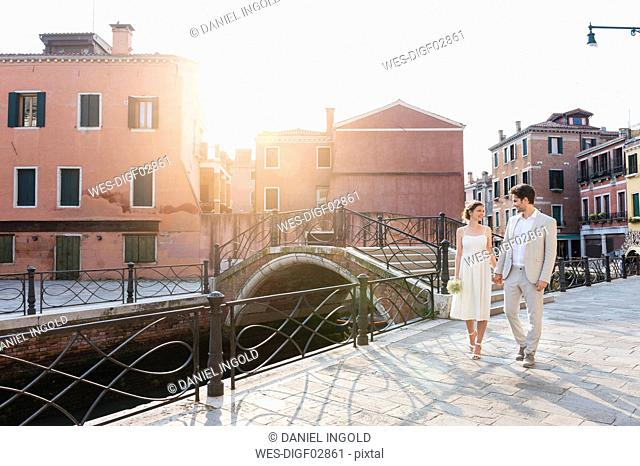 Italy, Venice, bridal couple walking hand in hand at sunrise