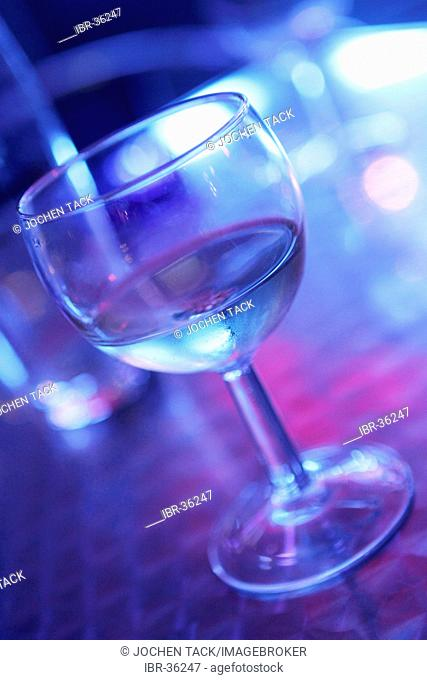 DEU, Germany: Glas of white wine in a bar, metal table, blue light