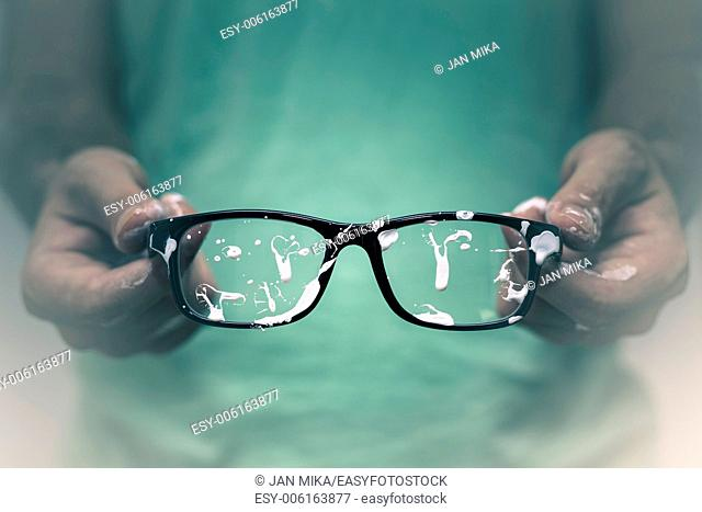 Creative vision concept. Closeup of creative man showing his stained eyeglasses