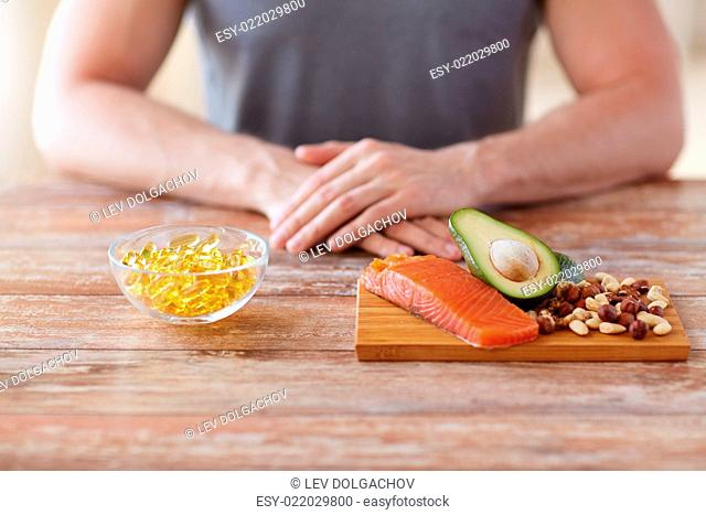 healthy eating, diet and people concept - close up of male hands with food rich in protein on cutting board on table