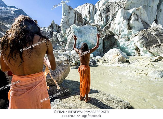 A Sadhu, holy man, is standing and praying on a rock at Gaumukh, the main source of the holy river Ganges, Gangotri, Uttarakhand, India