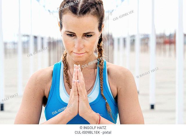 Woman practising yoga by beach